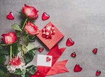 Jour de valentines, amour ou concept de datation Groupe de roses rouges avec le boîte-cadeau, la carte de voeux de papier blanc e Photographie stock