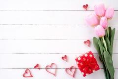 Jour de valentines et concept d'amour Coeurs de papier roses avec le boîte-cadeau et les tulipes rouges avec le ruban images stock
