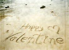 Jour de valentines heureux ! écrit en sable Image libre de droits