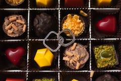 Jour du mariage Beaux anneaux du marié et de la jeune mariée dans une boîte avec les bonbons colorés Image libre de droits