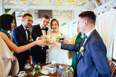 Jour du mariage de jeunes mariées avec des amis dans un café Photos stock