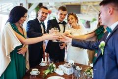 Jour du mariage de jeunes mariées avec des amis dans un café Image libre de droits