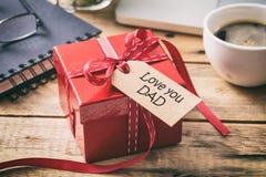 Jour du `s de père Boîte-cadeau rouge avec amour vous étiquette de papa, fond de bureau de tache floue Photos libres de droits