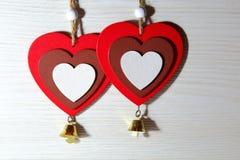 Jour du ` s de St Valentine, amour Deux coeurs rouges avec des cloches sur une lumière Photographie stock