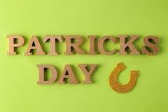 Jour du ` s de StPatrick célébration fer à cheval et texte d'or sur un fond vert clair Vue supérieure images stock