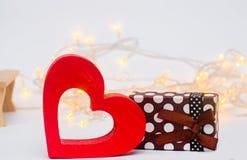 Jour du ` s de Valentine, amour de concept coeur en bois avec un cadeau sur un fond blanc Photos stock