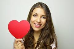 Jour du `s de Valentine Belle jeune femme dans l'amour tenant un coeur et un sourire de papier à l'appareil-photo sur le fond gri Photos libres de droits