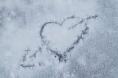 Jour du `s de Valentine Coeur percé par une flèche dessinée sur la neige Images stock
