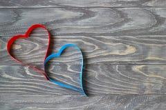 Jour du `s de Valentine Deux coeurs des rubans de rouge et de bleu sur un CCB Images stock