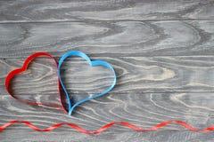 Jour du `s de Valentine Deux coeurs des rubans de rouge et de bleu sur un CCB Photographie stock libre de droits