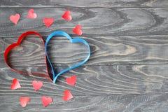 Jour du `s de Valentine Deux coeurs des rubans de rouge et de bleu sur un CCB Photos stock