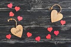 Jour du ` s de Valentine, deux coeurs en bois entourés par un petit coeur rouge sur un fond en bois noir Photos libres de droits