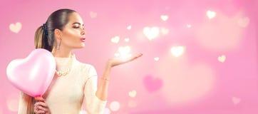 Jour du `s de Valentine Fille de beauté avec le ballon à air en forme de coeur rose dirigeant la main Photographie stock libre de droits