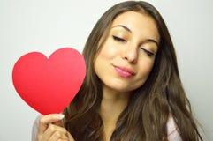 Jour du `s de Valentine Fille douce dans l'amour avec les yeux fermés tenant un coeur et un sourire de papier à l'appareil-photo  Photos libres de droits