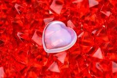 Jour du `s de Valentine Mensonges en verre blancs d'un coeur sur des cristaux de rouge-rubis au milieu Macro photographie image stock