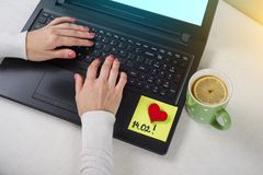 Jour du `s de Valentine note du texte 14 02 écrits sur un autocollant de papier Ordinateur de fond, ordinateur portable, mains du Photos libres de droits