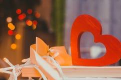 Jour du `s de Valentine un coeur en bois avec un arc jaune sur un fond de bokeh Le concept de l'amour lumière de vacances de guir Photographie stock