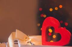 Jour du `s de Valentine un coeur en bois avec un arc jaune sur un fond de bokeh Le concept de l'amour lumière de vacances de guir Images libres de droits
