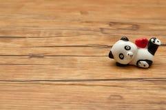 Jour du `s de Valentine Une figurine en céramique de panda tenant un coeur rouge Photos stock