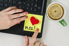 Jour du `s de Valentine Une note du texte 14 02 écrits sur un autocollant de papier Ordinateur de fond, ordinateur portable, main Photo stock