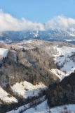 Jour ensoleillé d'un hiver, sur les collines sauvages de la Transylvanie avec des montagnes de Bucegi à l'arrière-plan Image libre de droits