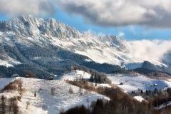 Jour ensoleillé d'un hiver, sur les collines sauvages de la Transylvanie avec des montagnes de Bucegi à l'arrière-plan Photos libres de droits