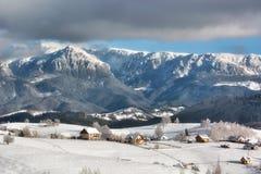 Jour ensoleillé d'un hiver, sur les collines sauvages de la Transylvanie avec des montagnes de Bucegi à l'arrière-plan Photo libre de droits