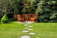 Jour ensoleillé dans un jardin de ressort avec la table et les bancs en bois Photographie stock