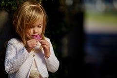 Jour ensoleillé, la petite fille se trouve sur l'herbe Image libre de droits