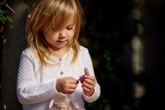 Jour ensoleillé, la petite fille se trouve sur l'herbe Photographie stock
