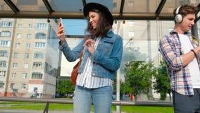 Jour ensoleillé, support de personnes à l'arrêt d'autobus avec des téléphones portables Attente du bus caméra sur le steadicame banque de vidéos