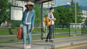 Jour ensoleillé, support de personnes à l'arrêt d'autobus avec des téléphones portables Attente du bus banque de vidéos