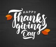 Jour heureux d'action de grâces Dirigez la carte de voeux avec des feuilles de lettrage et d'automne sur le fond de tableau noir Photos stock