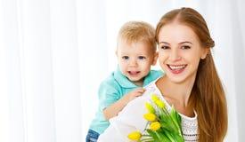 Jour heureux du `s de mère Le fils de bébé donne des fleurs pour la maman Images libres de droits