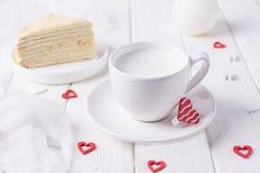 Jour heureux du `s de Valentine Tasse blanche avec du lait, le gâteau de miel fait maison et les coeurs rouges sur un fond blanc Photos stock