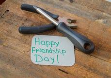 Jour heureux et outils d'amitié d'étiquettes sur le vieux fond en bois Photographie stock libre de droits