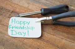 Jour heureux et outils d'amitié d'étiquettes sur le vieux fond en bois Photographie stock