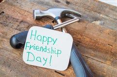 Jour heureux et outils d'amitié d'étiquettes sur le vieux fond en bois Photo stock