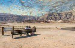 Jour nuageux en parc géologique de Timna, les couples des aînés regardent des montagnes Photographie stock libre de droits