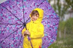 Jour pluvieux Fille heureuse d'enfant en bas âge portant le manteau imperméable avec le parapluie images libres de droits