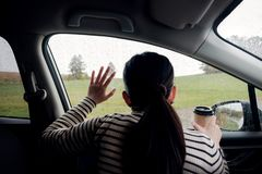 Jour pluvieux ou mauvais temps dans un concept de vacances une femme de tristesse avec du café chaud se reposant dans la voiture  photo stock