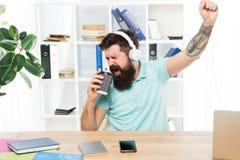 Jour régulier de bureau Les écouteurs barbus de type d'homme reposent le bureau écoutent musique chanter la chanson Le travailleu photographie stock