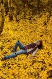 Jour rêvant dans des feuilles d'automne Photo libre de droits