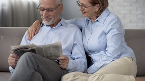 Journal âgé de lecture de mari, épouse l'étreignant avec amour, couple harmonieux photo stock