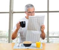 Journal âgé moyen du relevé d'homme avec le déjeuner Photos stock