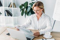 journal attrayant de sourire de lecture de femme d'affaires à la table avec l'ordinateur portable image libre de droits