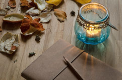 Journal with candle lantern and citrus peel. Notebook and a candle lantern on wooden table with dried fruit peel Royalty Free Stock Photos