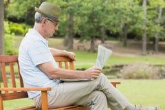 Journal décontracté de lecture d'homme supérieur au parc Photographie stock