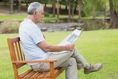 Journal décontracté de lecture d'homme supérieur au parc Photos stock