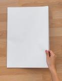 Journal de blanc de prise de main avec la moquerie vide de l'espace sur le backg en bois photos stock